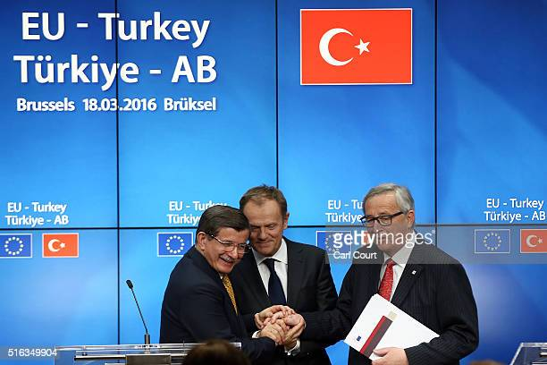 Turkey's Prime Minister Ahmet Davutoglu shakes hands with President of the European Council Donald Tusk and President of the European Commission...