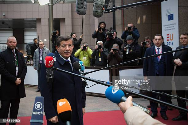 Turkey's Prime Minister Ahmet Davutoglu speaks to the media as he arrives at the Council of the European Union on the second day of an EU summit on...