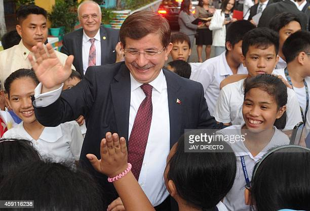 Turkey's Prime Minister Ahmet Davutoglu visits a government elementary school as he donated desktop and laptop computers in Manila on November 17...