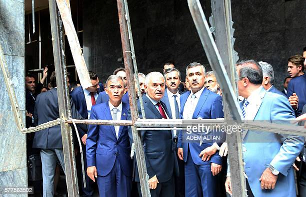 Turkey's Prime Minister Binali Yildirim gestures as he visits damaged parts of the Turkish parliament in Ankara, on July 19, 2016 in the aftermath of...