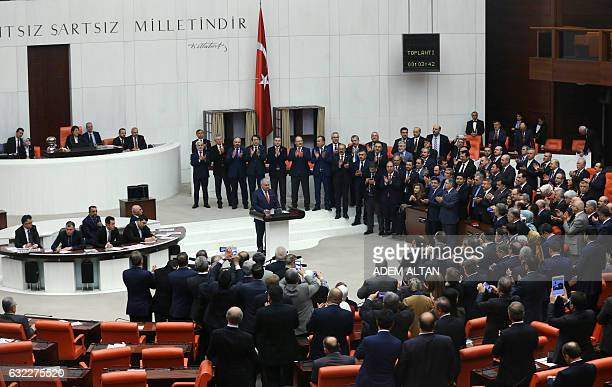 Turkey's Prime Minister Binali Yildirim is applauded by some of his lawmakers after Turkey's parliament approved a contentious constitutional reform...