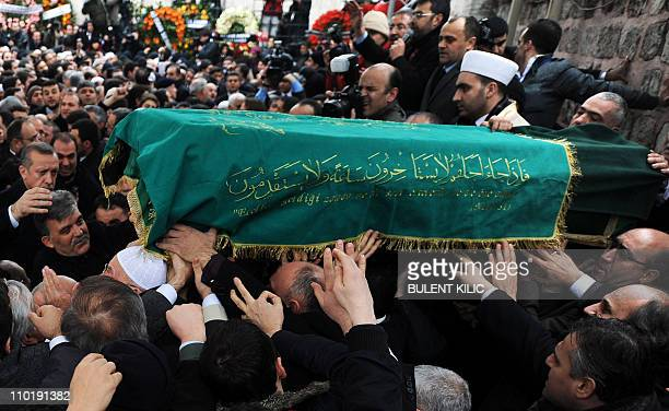 Turkey's Prime Minister Recep Tayyip Erdogan and President Abdullah Gul carry the coffin of late Prime Minister Necmettin Erbakan during his funeral...