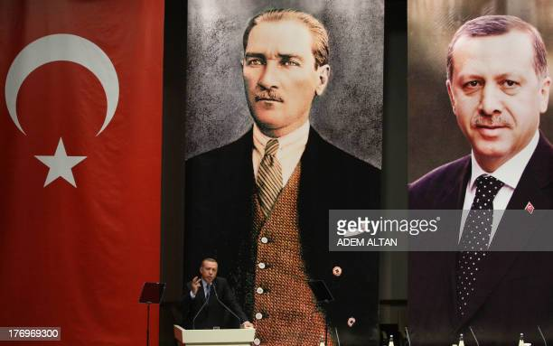 Turkey's Prime Minister Recep Tayyip Erdogan gestures as he gives a speech under a Turkish flag and portraits of himself and Mustafa Kemal Ataturk...