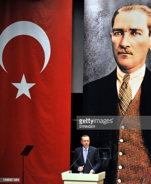 Turkey's Prime Minister Recep Tayyip Erdogan gestures as he speaks in front of a Turkish flag and a portrait of Mustafa Kemal Ataturk the founder of...
