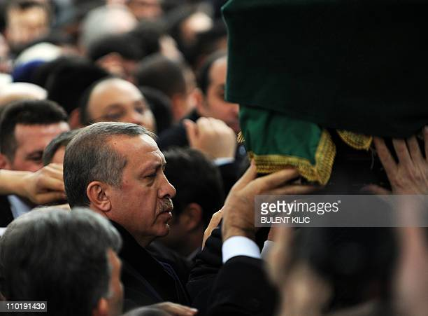 Turkey's Prime Minister Tayyip Erdogan touches the coffin of late Prime Minister Necmettin Erbakan during his funeral in Istanbul on March 1 2011...
