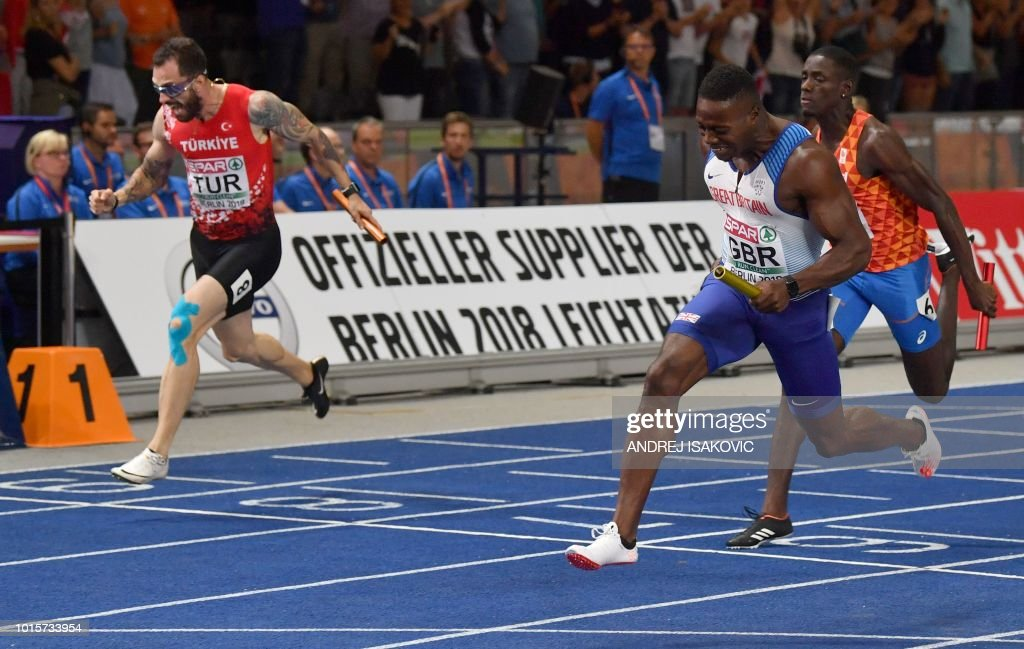 Turkey's Ramil Guliyev (2nd), Great Britain's Harry Aikines-Aryeetey (1st) and Netherlands' Taymir Burnet (3rd) cross the finish line of the men's 4x100m relay final during the European Athletics Championships at the Olympic stadium in Berlin on August 12, 2018.