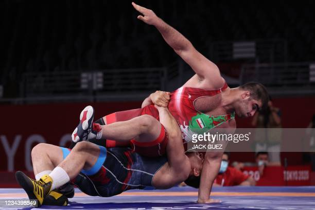 Turkey's Riza Kayaalp wrestles Iran's Amin Mirzazadeh in their men's greco-roman 130kg wrestling bronze medal match during the Tokyo 2020 Olympic...
