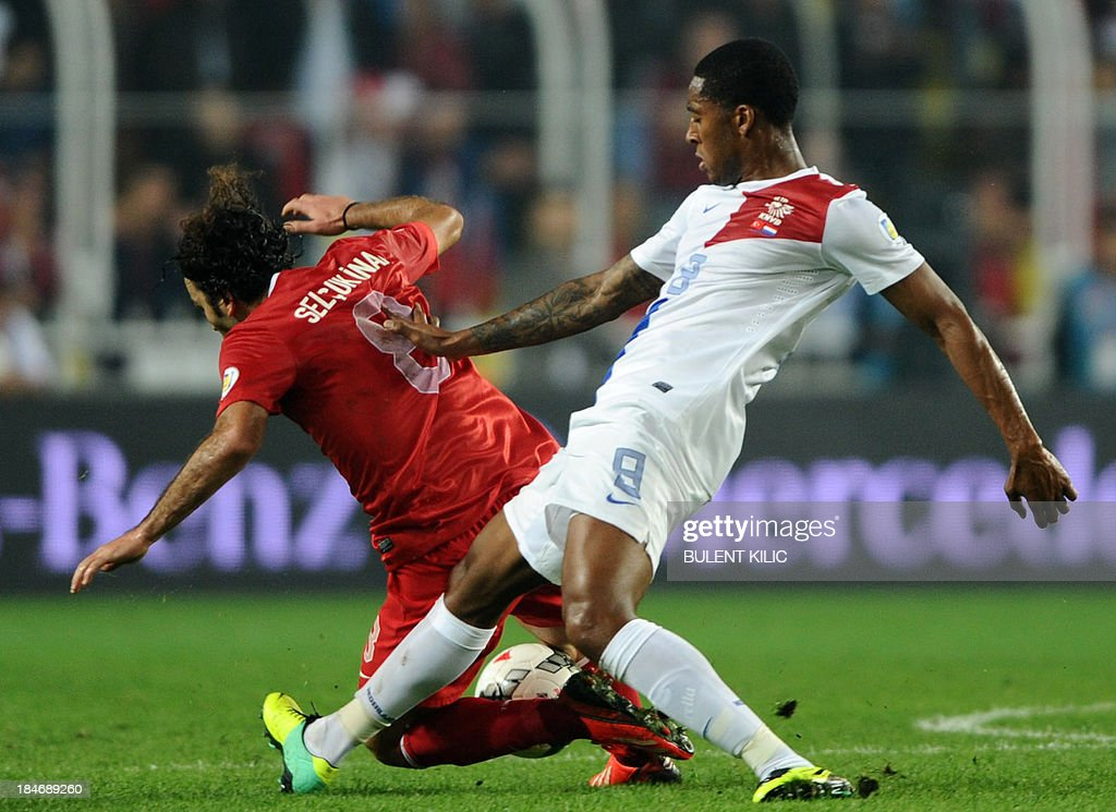 Turkey's Selcuk Inan (L) fights for the ball with Netherlands' Leroy Fer on October 15, 2013 during a FIFA 2014 World Cup qualifying football match at the Sukru Saracoglu Stadium in Istanbul.