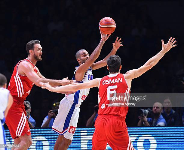 Turkey's Semih Erden and Cedi Osman vie against France's Tony Parker during the EuroBasket 2015 Round of 16 match between France and Turkey at the...