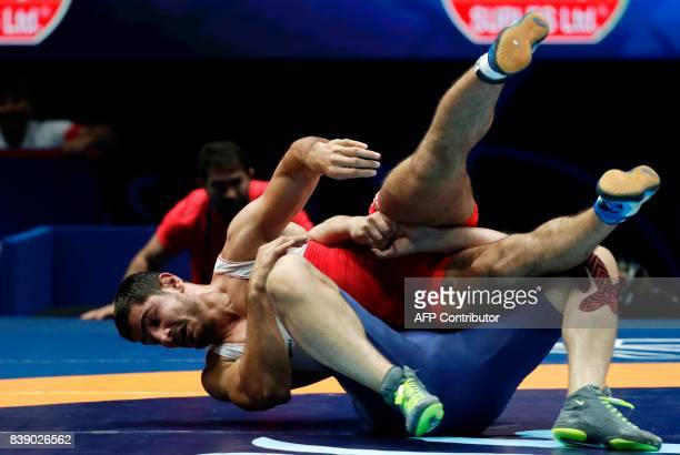 Turkey's Taha Akgul competes with Georgia's Geno Petriashvili during the men's freestyle wrestling Seniors 125kg category final of the FILA World...