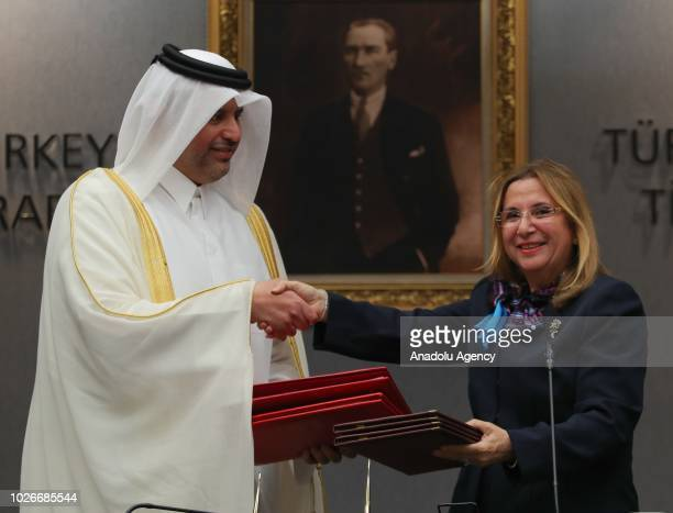 Turkey's Trade Minister Ruhsar Pekcan and Qatar's Economy and Commerce Minister Sheikh Ahmed bin Jassim bin Mohammed Al Thani shake hands after...
