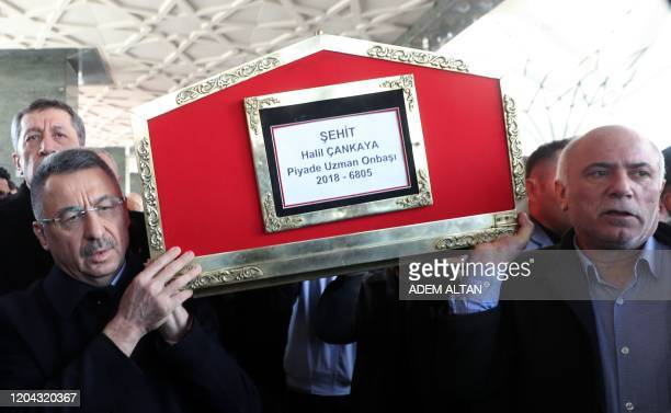 Turkey's Vice President Fuat Oktay carries the coffin of Turkish soldier Halil Cankaya, who was killed in an airstrike in the Syrian town of Idlib,...