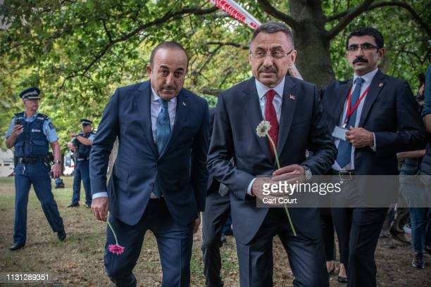 Turkey's Vice-President Fuat Oktay and Foreign Minister Mevlut Cavusoglu carry flowers to lay near Al Noor mosque on March 18, 2019 in Christchurch,...