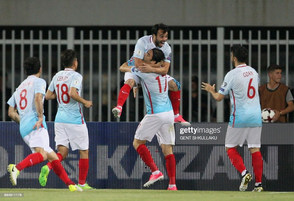 Turkey's Volkan Sen (TOP) celebrates with teammates including Burak Yilmaz (C/17) after scoring during the FIFA World Cup 2018 qualification football match between Kosovo and Turkey at Loro Borici stadium in Shkoder on June 11, 2017. / AFP PHOTO / Gent SHKULLAKU