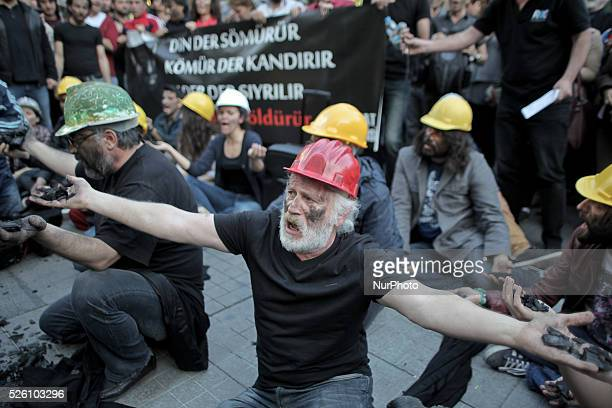 Turkish activists hold coal as they stained their faces with coal and wearing a miner's helmet during a demonstration for the victims of the Soma...