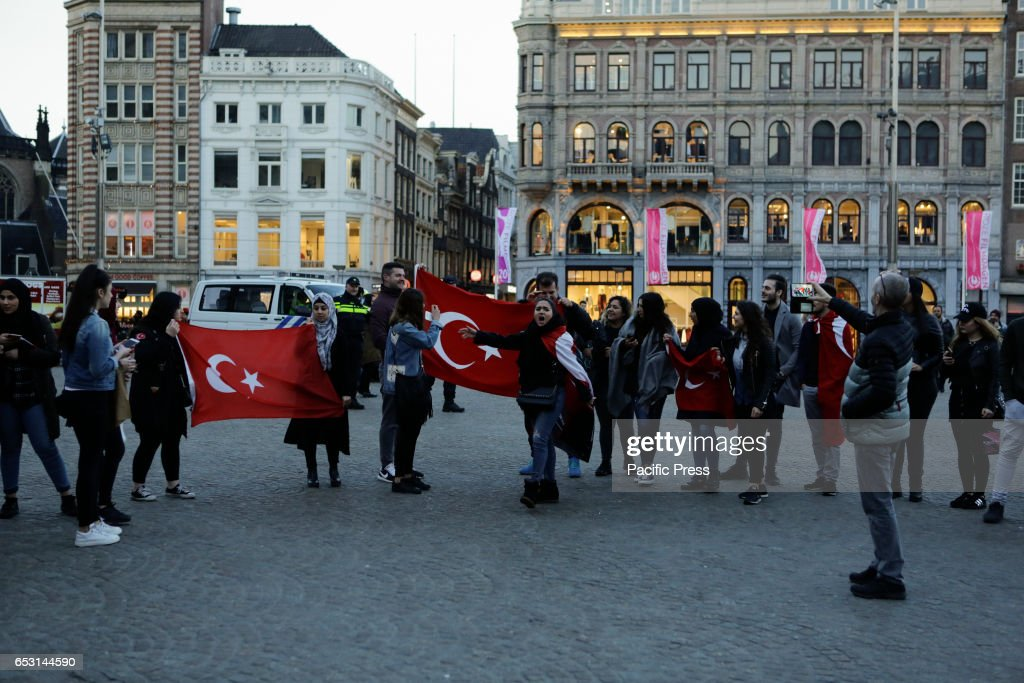 Turkish activists protest with Turkish flags at Dam Square. Around 20 Turkish nationalists protested peacefully at Amsterdams Dam square against the decision by the Dutch government to prevent two Turkish politicians to appear at rallies in the Netherlands.