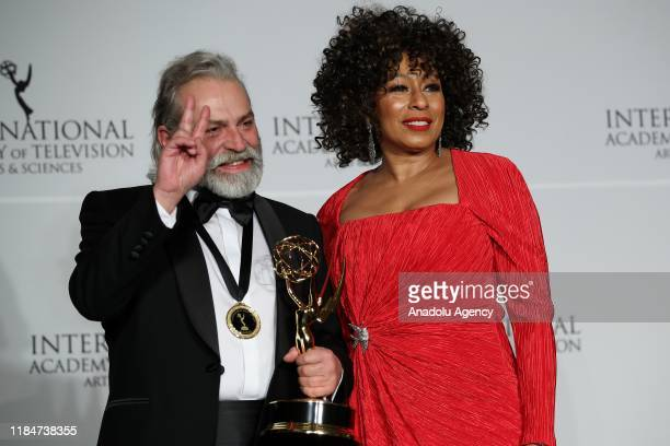 Turkish Actor Haluk Bilginer poses for a photo with US actress Tamara Tunie after he won the Best Performance by an Actor award on Monday at the 47th...
