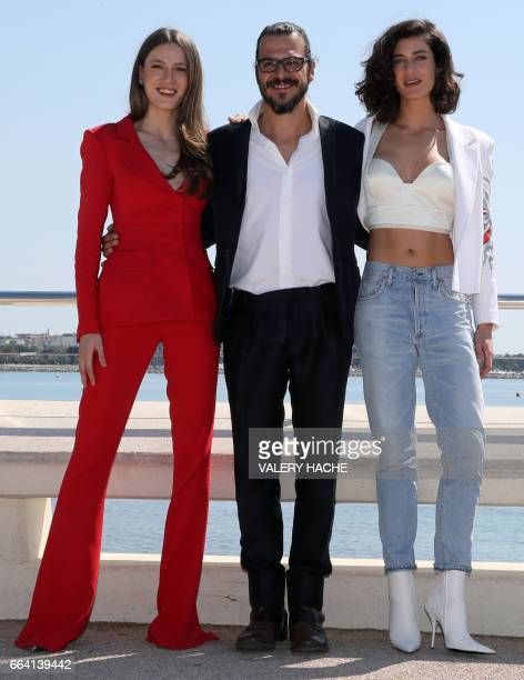 Turkish actors Seranay Sarikaya Mehmet Gunsur and Berrak Tuzunatac who star in the series 'Phi' pose during a photocall as part of the MIPTV event on...