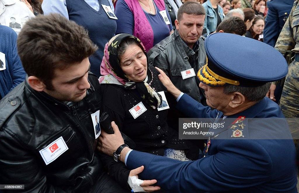 Turkish Air Force Commander Gen. Akin Ozturk (R) offer condolences to Master Sergeant Nejdet Aydogdu's mother Selma Aydogdu (C) during the funeral ceremony at Diyarbakr 8th Main Air Base Command in Diyarbakir, Turkey on October 30, 2014. A statement on October 29, 2014 from the Turkish General Staff said Master Sergeant Nejdet Aydogdu had been shot in the head at close range by two masked men in a market.