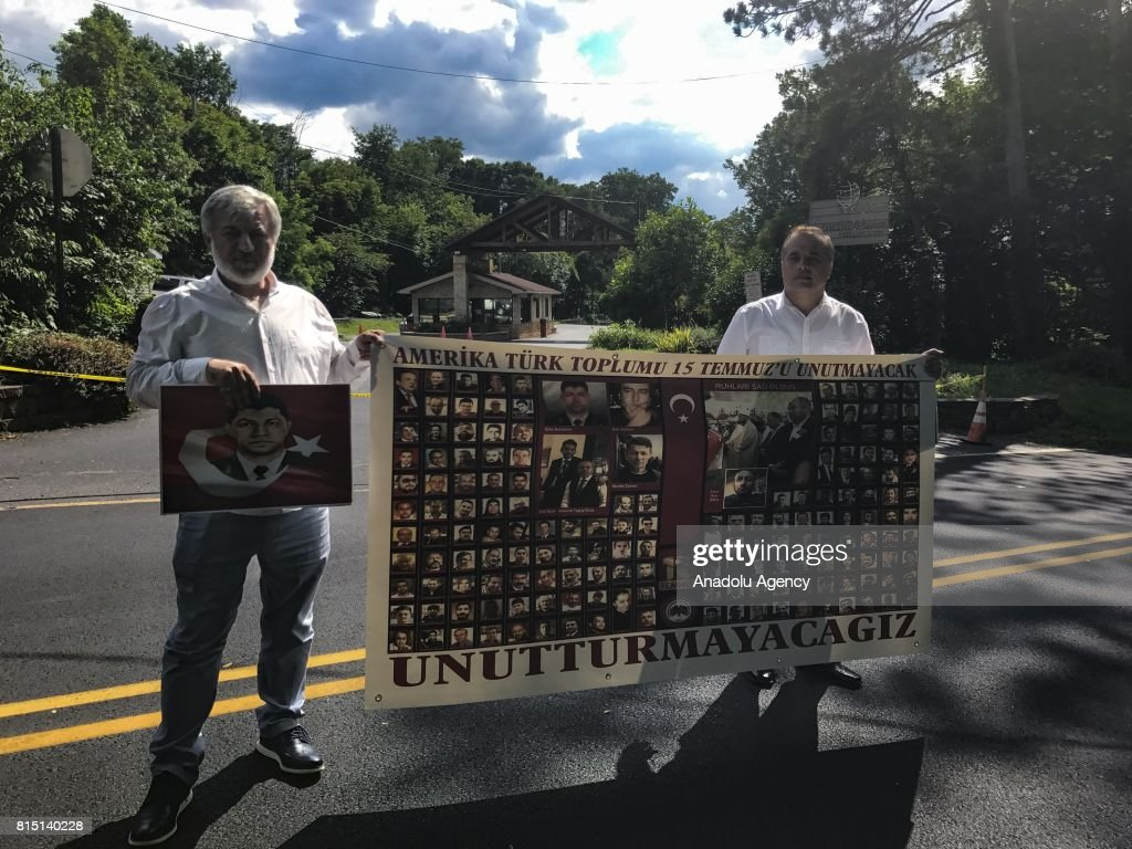 Turkish Americans hold images of July 15 martyrs with 'American Turkish Society Will Not Forget July 15, Nor Let It Be Forgotten' written in Turkish outside of the Fetullah Terrorist Organization (FETO) compound where Fetulah Gulen resides in Saylorsburg, PA., United States on July 15, 2017. 249 people were martyred and nearly 2,200 people injured in the defeated 15th of July 2016 coup attempt, which the Turkish government said was carried out by the Fetullah Terrorist Organization (FETO) led by U.S.-based Turkish citizen Fetullah Gulen. Turkish officials accuse Fetullah Gulen plotting to overthrow the government of President Erdogan as the culmination of a long running campaign to infiltrate Turkish institutions including the military, the police and the judiciary.