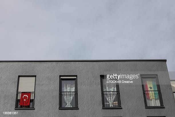 turkish and ghanaian flag at windows of an apartment building, munich, bavaria, germany - ghanaian flag stock photos and pictures