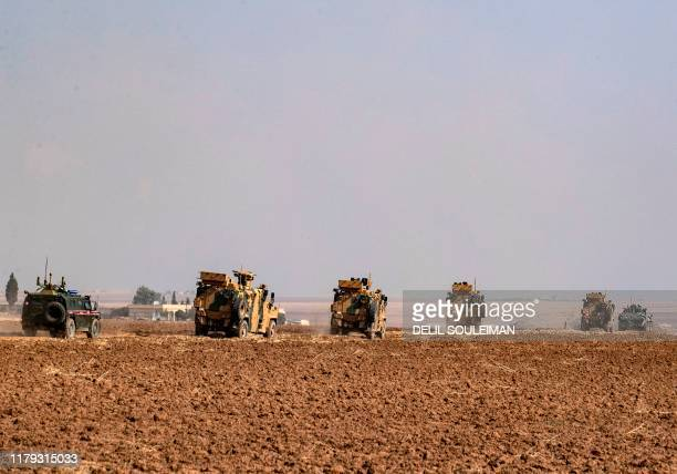 TOPSHOT Turkish and Russian military vehicles drive on a joint patrol in the countryside of Darbasiyah town in Syria's northeastern Hasakeh province...