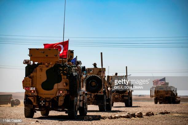 Turkish and US military vehicles drive on a joint patrol in the Syrian village of al-Hashisha on the outskirts of Tal Abyad town on the border with...