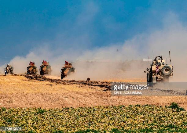 Turkish and US military vehicles, take part in joint patrol in the Syrian village of al-Hashisha on the outskirts of Tal Abyad town along the border...