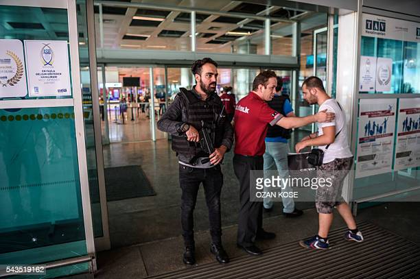 A Turkish anti riot police officer and an employee of a private security company patrols check as passengers enter the Ataturk airport International...