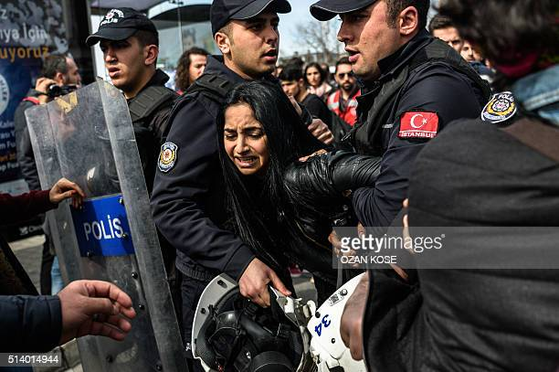 TOPSHOT Turkish anti riot police officers detain a woman on March 6 during a march in Kadikoy district in Istanbul to mark International Women's Day...