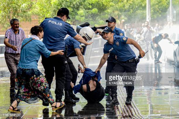 Turkish anti riot police officers try to detain a demonstrator during a protest against the replacement of Kurdish mayors with state officials in...