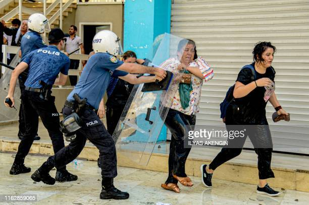 Turkish anti riot police officers use their shields to disperse demonstrators during a protest against the replacement of Kurdish mayors with state...