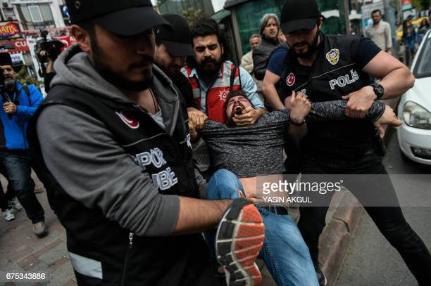TOPSHOT Turkish antiriot police arrest a protester attempting to defy a ban and march on Taksim Square to celebrate May Day in Istanbul on May 1 2017...
