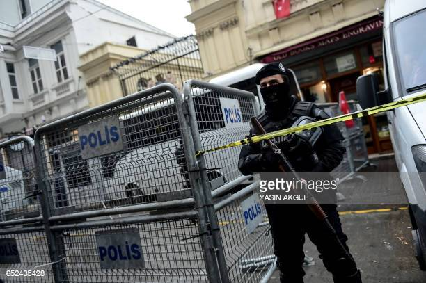 A Turkish antiriot police officer stands guard as protesters demonstrate in front of the Dutch Consulate on March 12 2017 in Istanbul Protestors...