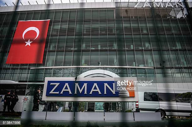 Turkish antiriot police officers are seen through a fence standing guard at the headquarters of Turkish daily newspaper Zaman in Istanbul on March 5...
