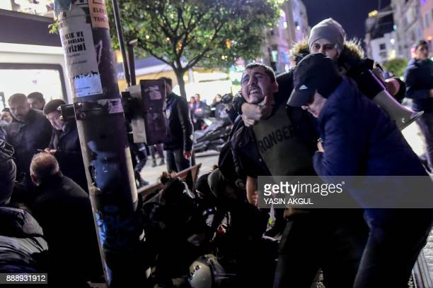Turkish antiriot police officers detain a leftist protester during a demonstration against the US and Israel on December 9 2017 in the Kadikoy...