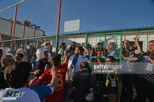 Turkish antiriot police officers guard Erzurum's players on May 16 2017 after they won the Turkish Super Lig white group semifinal second leg...
