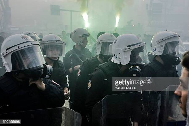 Turkish anti-riot police stand next to burning torch before the Turkish Spor Toto Super league football match between Besiktas and Bursaspor at...