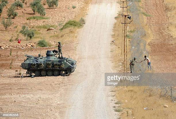 Turkish APC controls the borderline as a Turkish soldier TurkishSyrian talks with a Kurdish Syrian refrugee man near the southeastern town of Suruc...