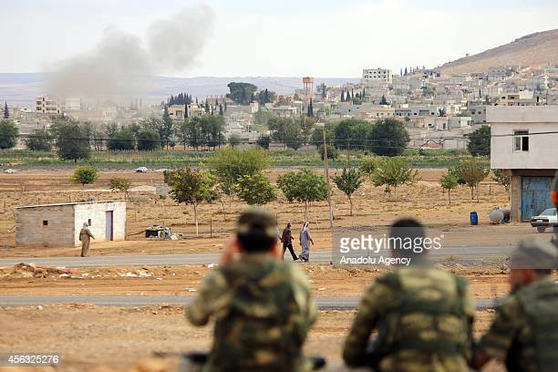 Turkish Armed Forces watches the clashes between the Kurdish armed troops and Islamic State of Iraq and the Levant with his binoculars in Suruc...