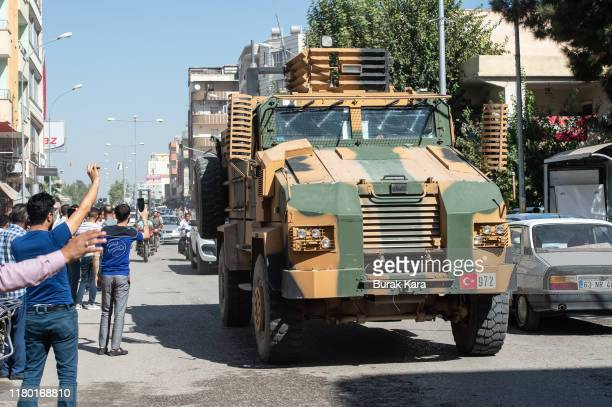 Turkish armoured vehicles escort members of the Turkish-backed Free Syrian Army, a militant group active in parts of northwest Syria, as they cross...