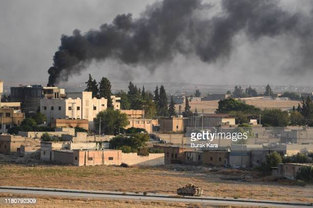 Turkish army armored vehicle advances in the Syrian city of Tel Abyad, as seen from the Turkish border town of Akcakale on October 13, 2019 in...