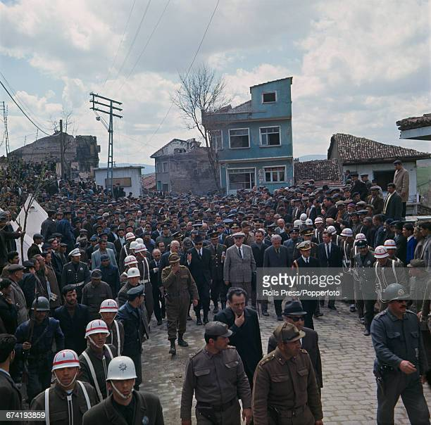 Turkish army officer and President of Turkey Cevdet Sunay pictured centre in grey suit and large cap makes a visit to the earthquake hit town of...