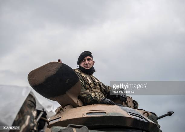 Turkish army soldier sits a tank waiting near the Syrian border before entering neighbouring Syria on January 21 2018 at Hassa in Hatay province...
