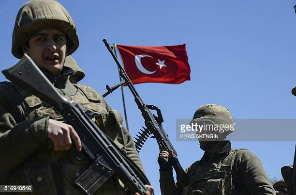 Turkish army soldiers stand guard as Kurdish people wait in a hope to enter Cizre a town subject to a curfew as part of a controversial operation...