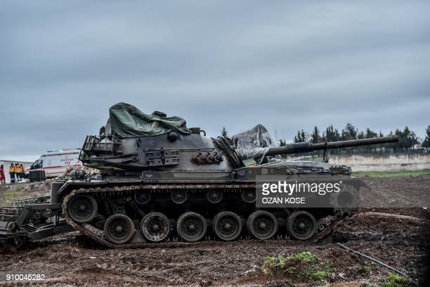 A Turkish army tank is stationed in a field near the Syrian border at Hassa in Hatay province on January 25 as part of the operation 'Olive Branch'...