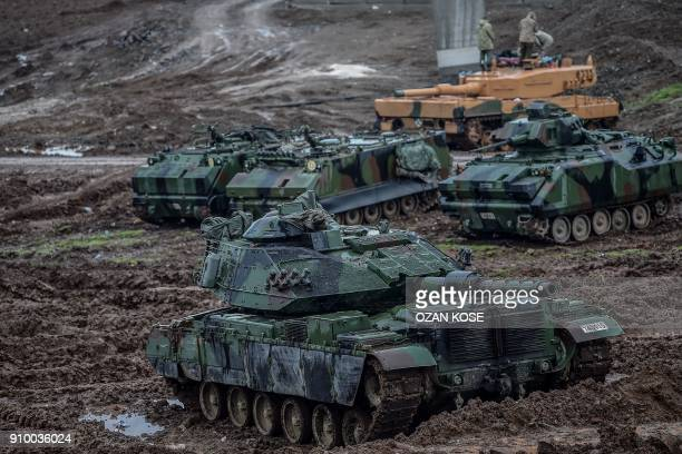 Turkish army tanks are stationed in a field near the Syrian border at Hassa in Hatay province on January 25 as part of the operation 'Olive Branch'...