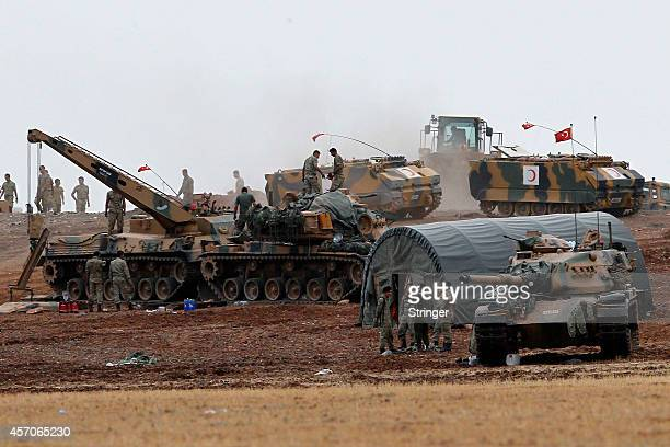 Turkish army tanks mechanized units take position on top of a hill near Mursitpinar border crossing in the southeastern Turkish town of Suruc in...