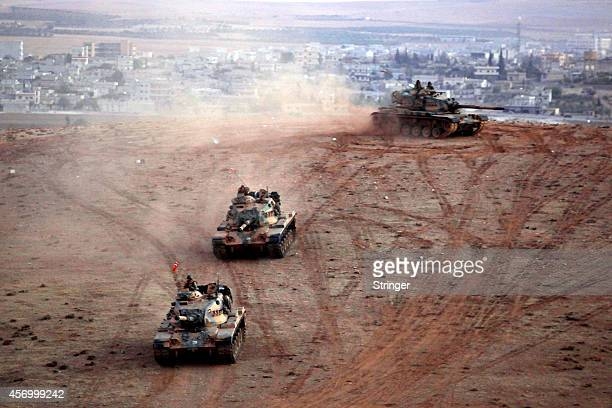 Turkish army tanks watch from their positions on a hilltop with the Syrian town of Kobani in the background as seen from the southeastern town of...