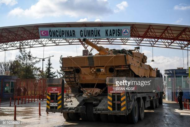 Turkish army truck carrying a tank drives through the Oncupinar border crossing close to the Turkish town of Kilis on January 27 as troops enter...